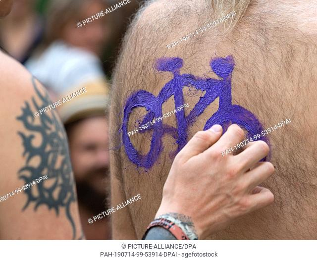 """14 July 2019, Berlin: Danny paints Holger a purple bicycle on his hairy back during the body painting during the protest action """"""""2nd Berlin Bikini and Swimsuit..."""
