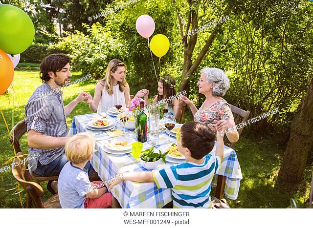 Family of three generations praying at a garden party