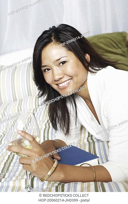 Portrait of a young woman holding a wineglass smiling