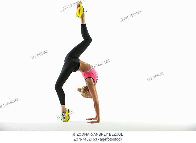 Rhythmic gymnast in a beautiful sportswear doing exercise in studio