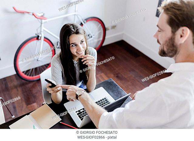 Smiling couple with laptop and cell phone at home talking