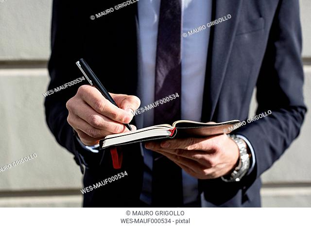 Businessman outdoors writing in diary