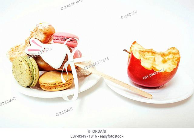 new diet concept, question sign in shape of measurment tape between red apple and donut, cake, macaroon isolated on white