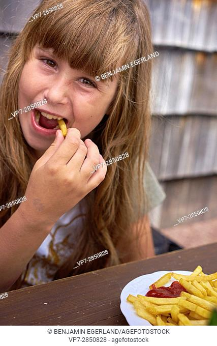 happy young girl eating French Fries with ketchup