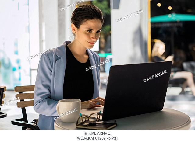 Young businesswoman sitting in coffee shop, using laptop