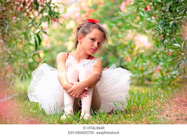 Girl dressed for ballet sitting on the grass in the park