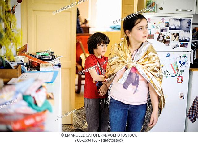 Little girl with luminescent paper cloak playing at home with his brother