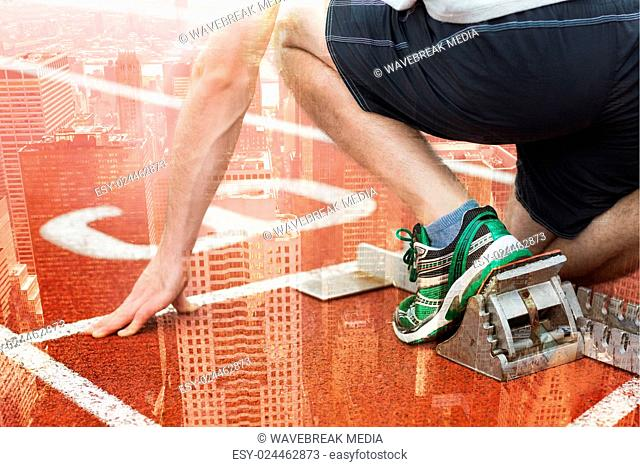 Composite image of mid section of a man ready to race on running track