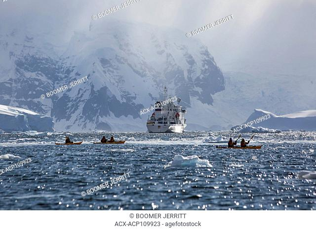 Kayakers paddle in Wilhelmina Bay as Akademic Vavilov remains at anchor against a dramatic backdrop, Gerlache Strait, Antarctic Peninsula