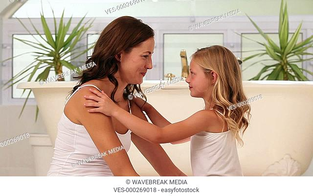 Little girl giving her mother a hug and kiss