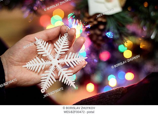 Woman's hand holding Christmas ornament, close-up