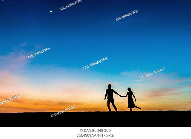 Silhouetted view of romantic mid adult couple holding hands at dusk, Maspalomas, Gran Canaria, Canary Islands, Spain