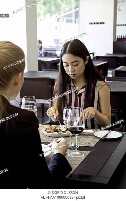 Woman dining in restaurant with friend