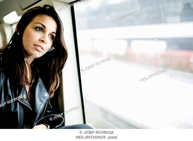 Young woman on train looking out of window