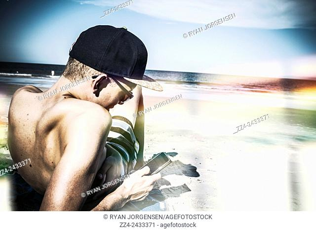 Artistic technology lifestyle portrait of a man using mobile smart phone when navigating via a wireless internet connection by the ocean