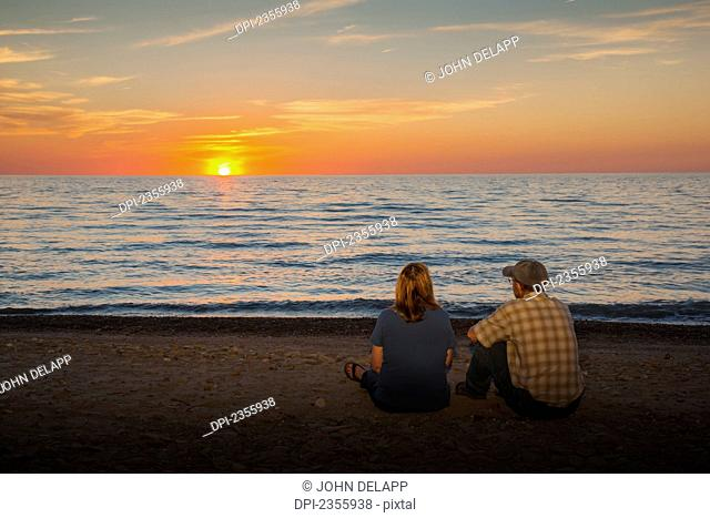 A man and woman sit on a beach watching the sunset on Lake Erie, Presque Isle State Park; Erie, Pennsylvania, United States of America