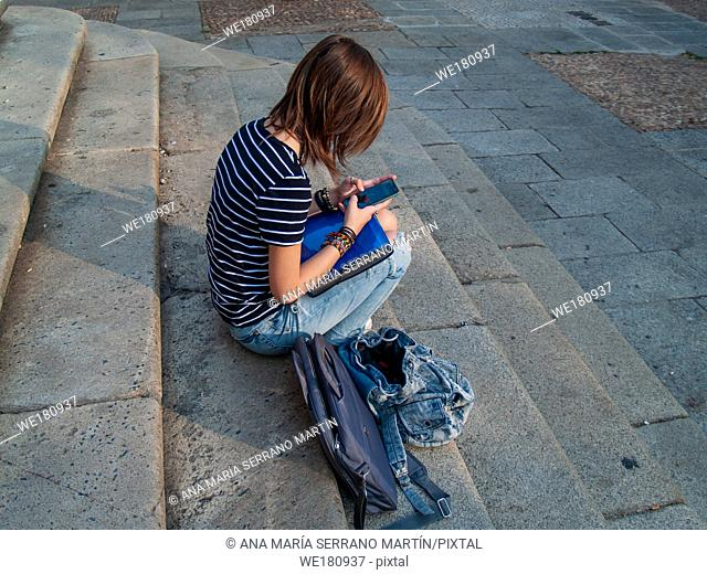 A teenage woman with a smart phone on her hands on the stairs of an historial building