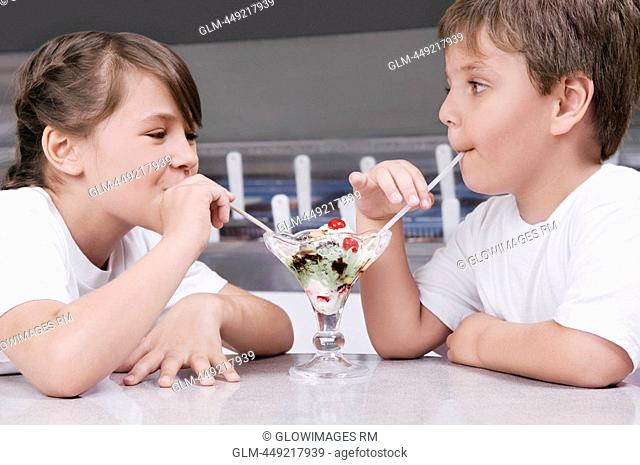 Boy and a girl sharing ice cream in an ice cream parlor