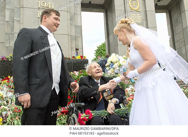 A Soviet veteran talks to a bride and groom in front of the Soviet Memorial on the Strasse des 17. Juni (lit. Street of June 17th) in Berlin, Germany