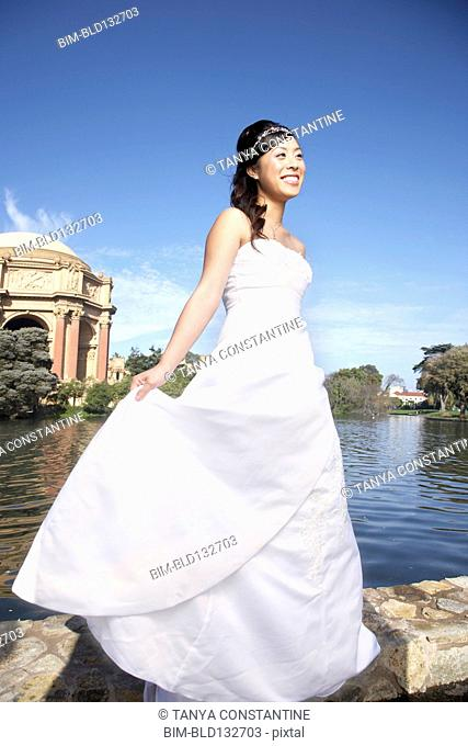 Chinese bride smiling in urban park, San Francisco, California, United States