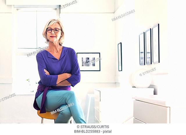 Confident Caucasian woman sitting on stool