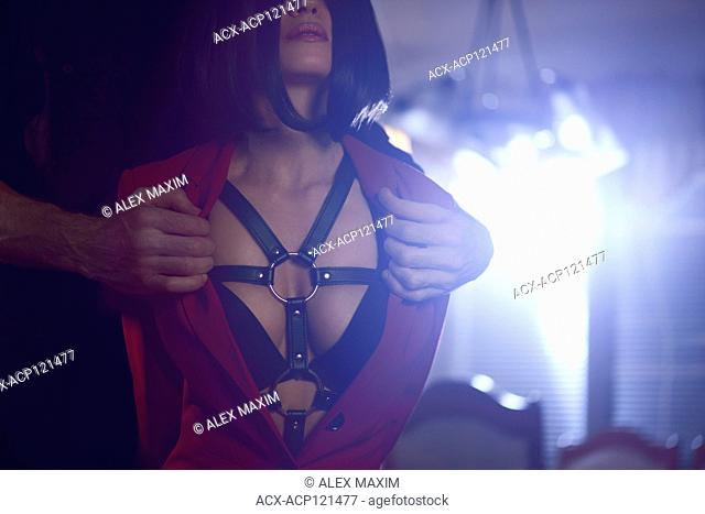 Sexy couple artistic sensual portrait of man hands undressing beautiful young seductive woman revealing leather bondage harness and underwear in glowing night...