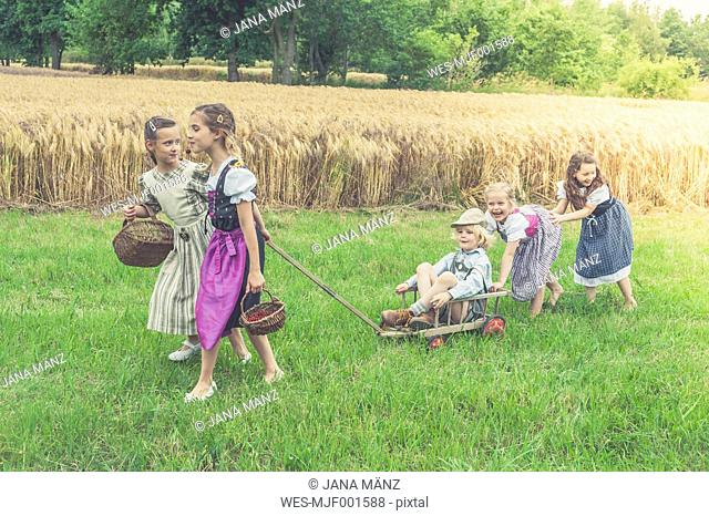 Germany, Saxony, five children with trolley on a meadow