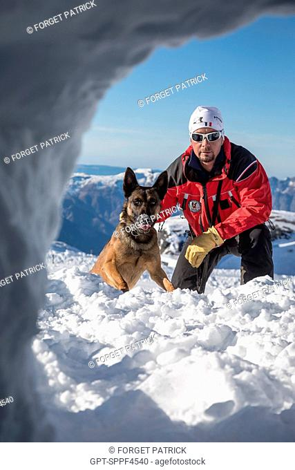 JEAN-MICHEL MORLOT AND HIS BELGIAN MALINOIS NAMED JEEP IN FRONT OF AN OPENING IN THE SNOW LOOKING FOR A VICTIM, REPORTING ON AVALANCHE DOG HANDLERS
