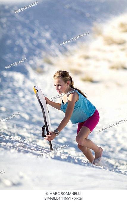 Caucasian girl climbing sand dune with sled