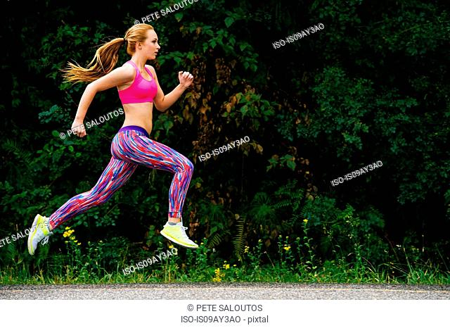Teenage female runner running on rural road