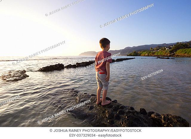 Lifestyle portrait of a young boy standing on a ledge submerged in the water of the Pacific Ocean in Oahu Hawaii