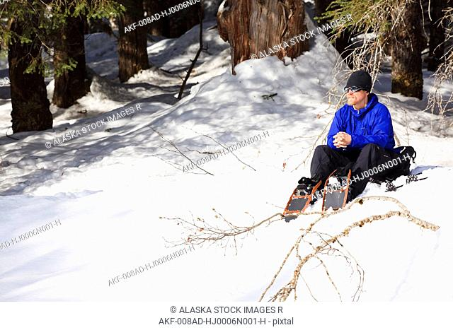Man snowshoeing rests on the bank of Andrews Creek in the sun, Tongass National Forest in Stikine-LeConte Wilderness, Southeast Alaska