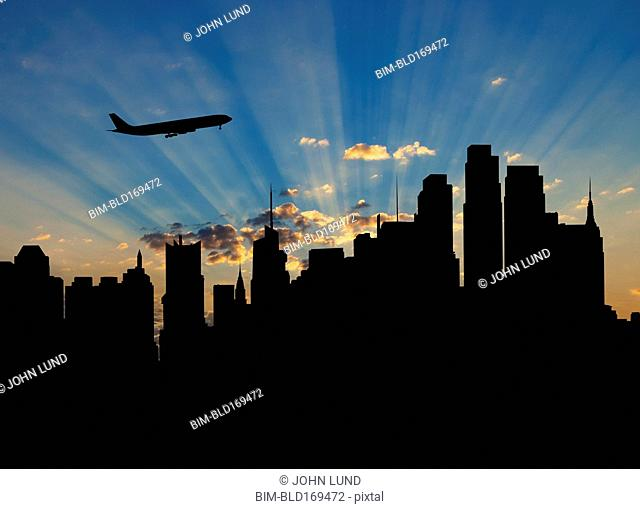 Silhouette of airplane flying over city skyline