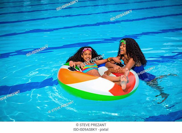 Girls in swimming pool playing with inflatable ring, smiling