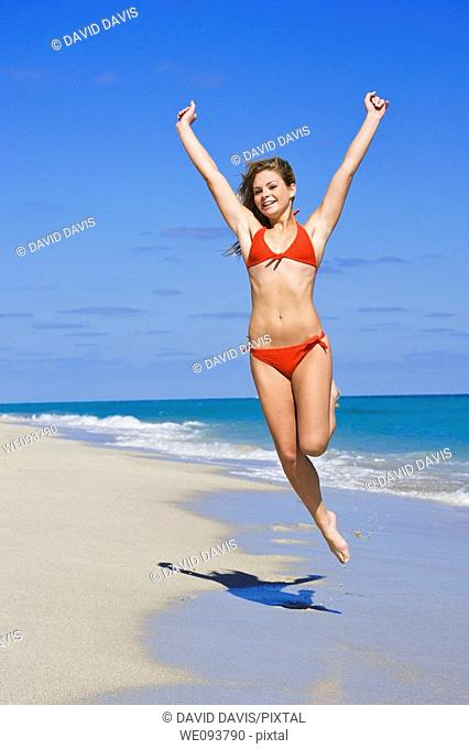 Beautiful Caucasian female teenage having fun on South Beach jumping into the air wearing a swimsuit