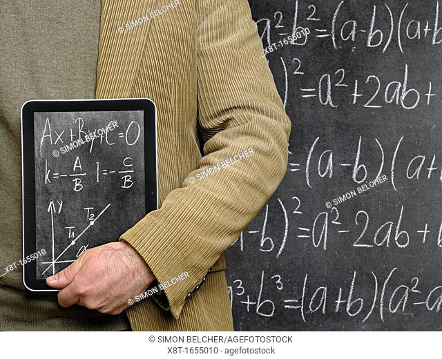 Teacher Holding a Tablet Computer in Front of a Chalkboard