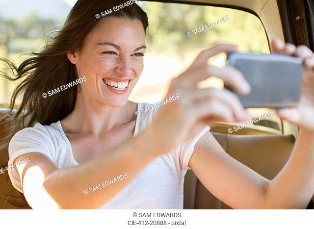 Woman riding in car taking picture with cell phone