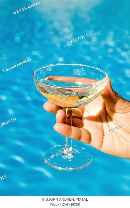 Hand holding champagne glass in front of pool