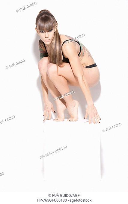 Young sporty woman on white pedestal