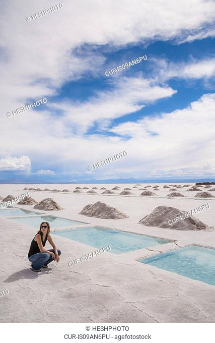 Woman sitting by pools in a salt field, Salinas Grandes, Cordoba Province, Argentina