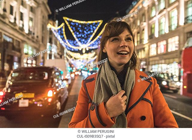 Young woman walking along illuminated street, smiling