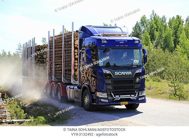Test drivers wave as they drive Next Generation Scania R730 logging truck on rural road during Scania Tour 2018 in Lohja, Finland - May 25, 2018