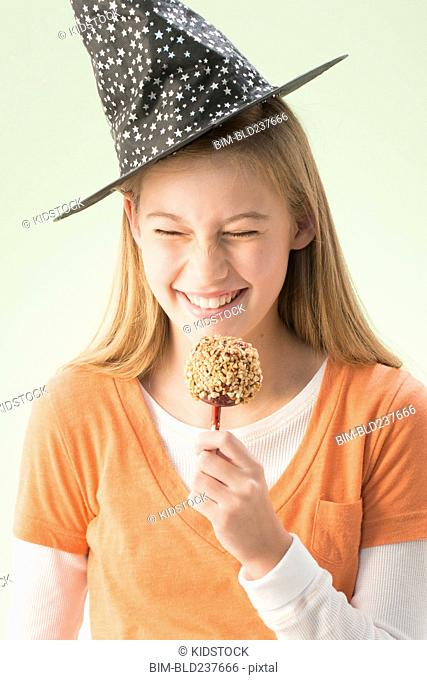 Caucasian girl wearing witch hat eating candy apple