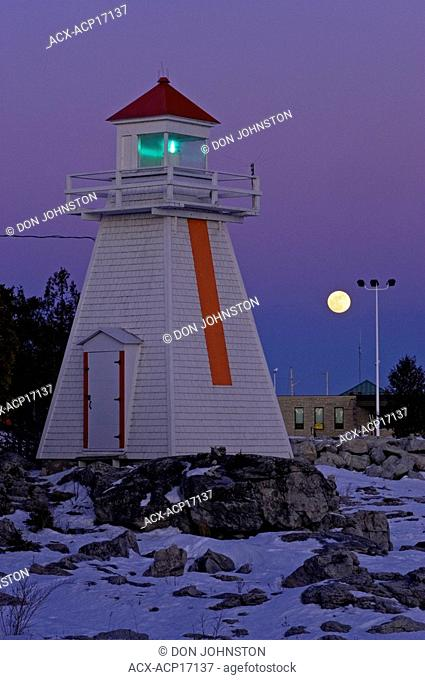 Moonrise over lighthouse and ferry terminal buildings, South Bay, Manitoulin Island, Ontario, Canada