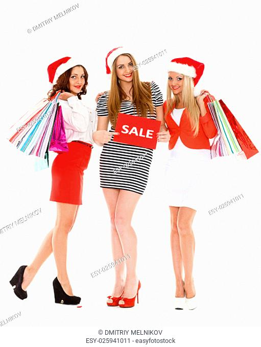 Three pretty young women in Santa's hat with shopping bags stand on a white background. Christmas sale