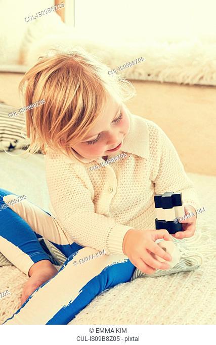 Female toddler sitting on bed stacking building bricks