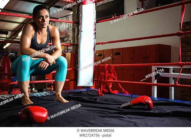 Thoughtful female boxer sitting on rope
