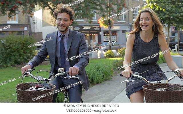 Businesswoman and businessman riding bike through urban park.Shot on Canon 5D MkII at a frame rate of 25fps