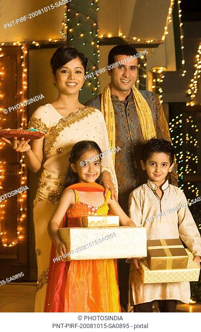 Children holding gifts with their parents holding religious offering