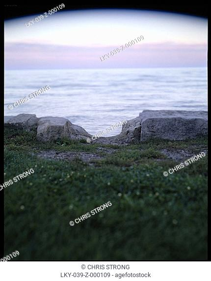 Low-angle shot of cliff edge overlooking water